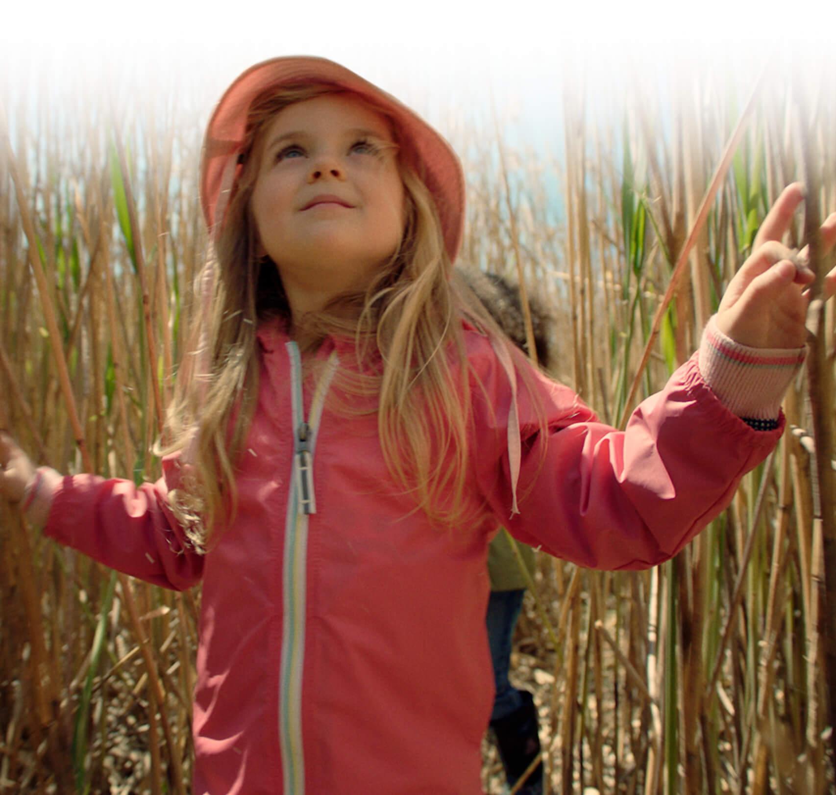 Une petite fille avec manteau et chapeau roses, se balade dans un champ de maïs avec son amie.