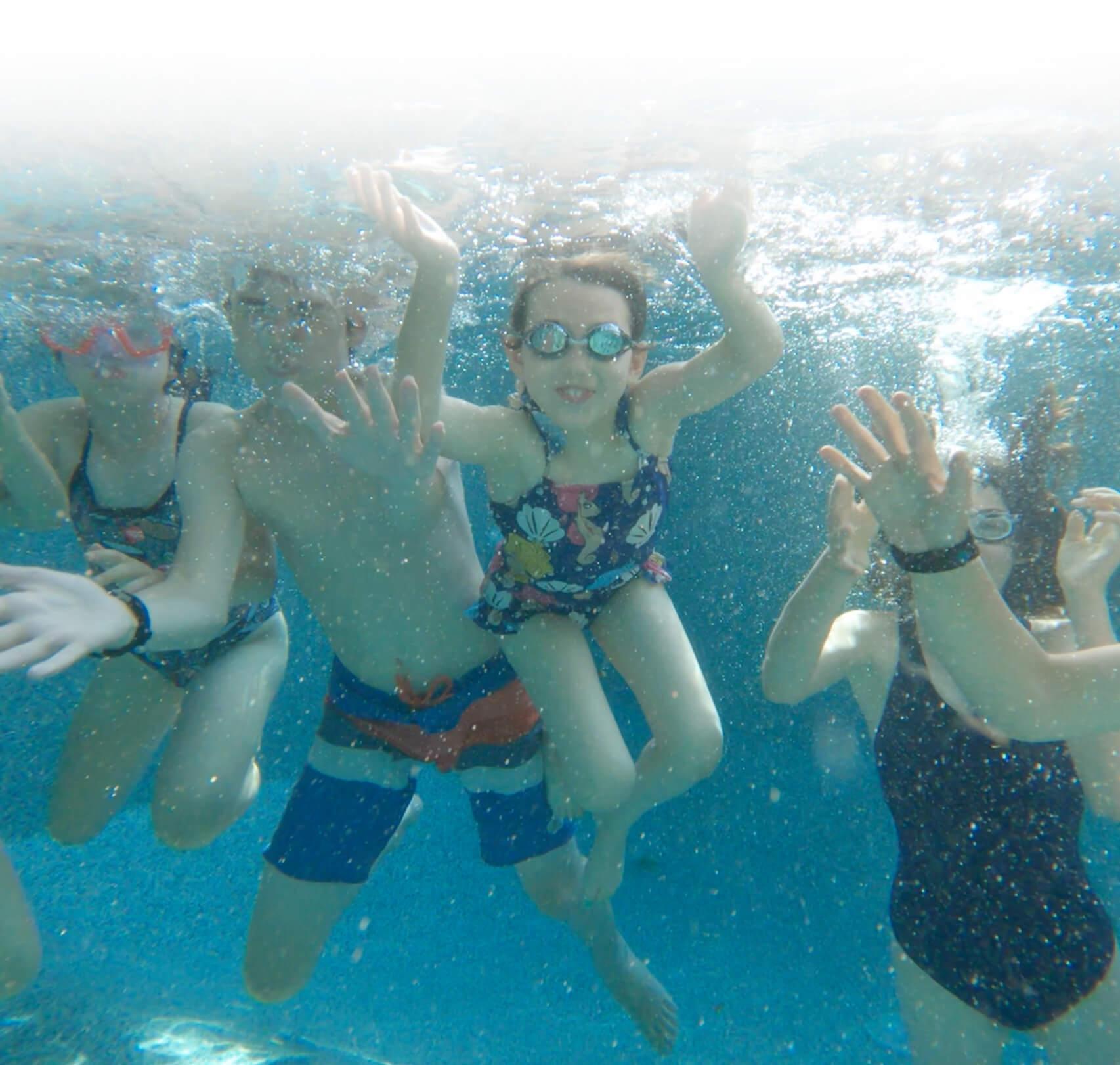 Quatre enfants se baignent et font un coucou à la caméra dans l'eau.