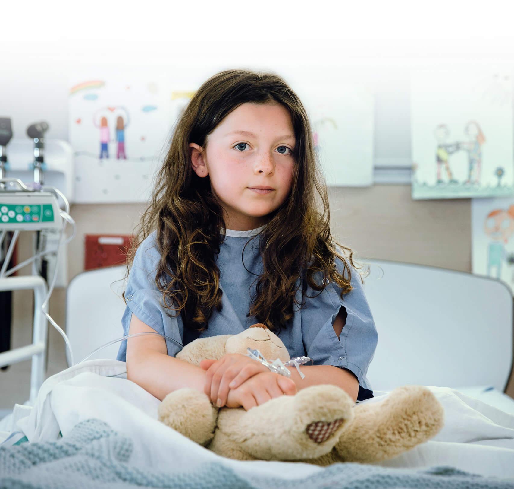 Romy Jade, 8 ans, montre un regard triste alors qu'elle est assise dans son lit à l'hôpital avec son ourson en peluche dans les mains.