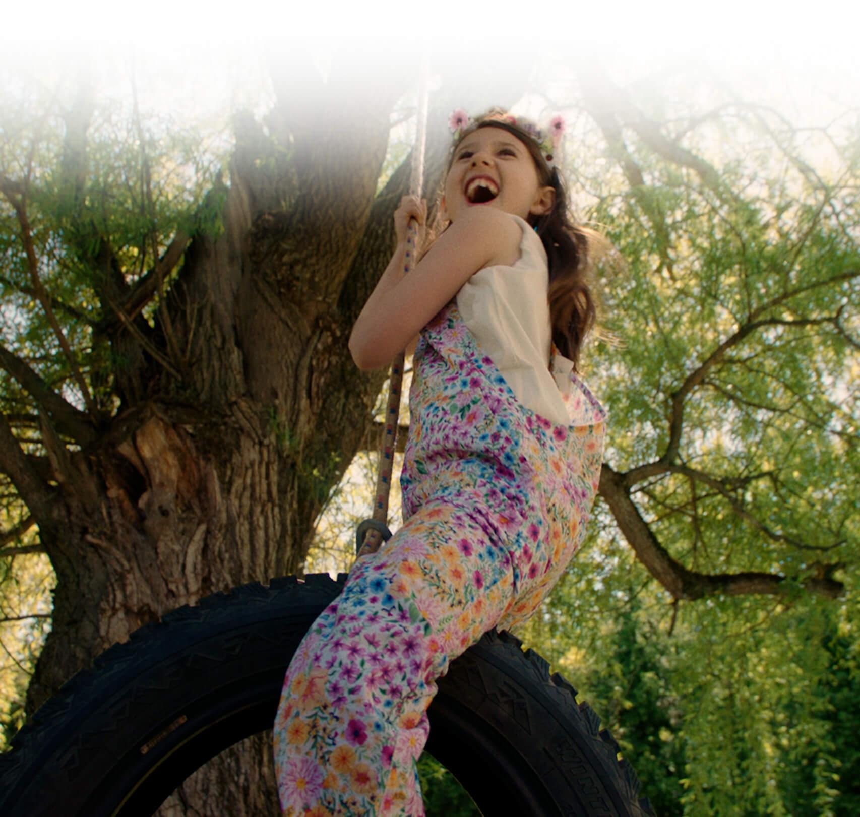 Une enfant tout sourire se balance à un arbre.