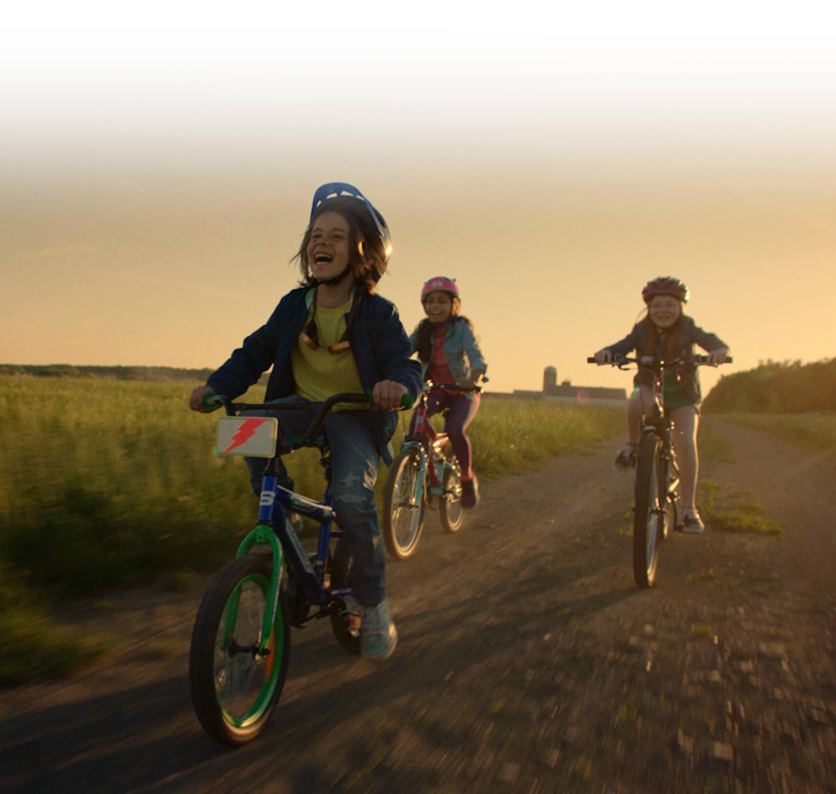 Deux enfants à vélo sillonnent avec enthousiasme un chemin de campagne au coucher du soleil.