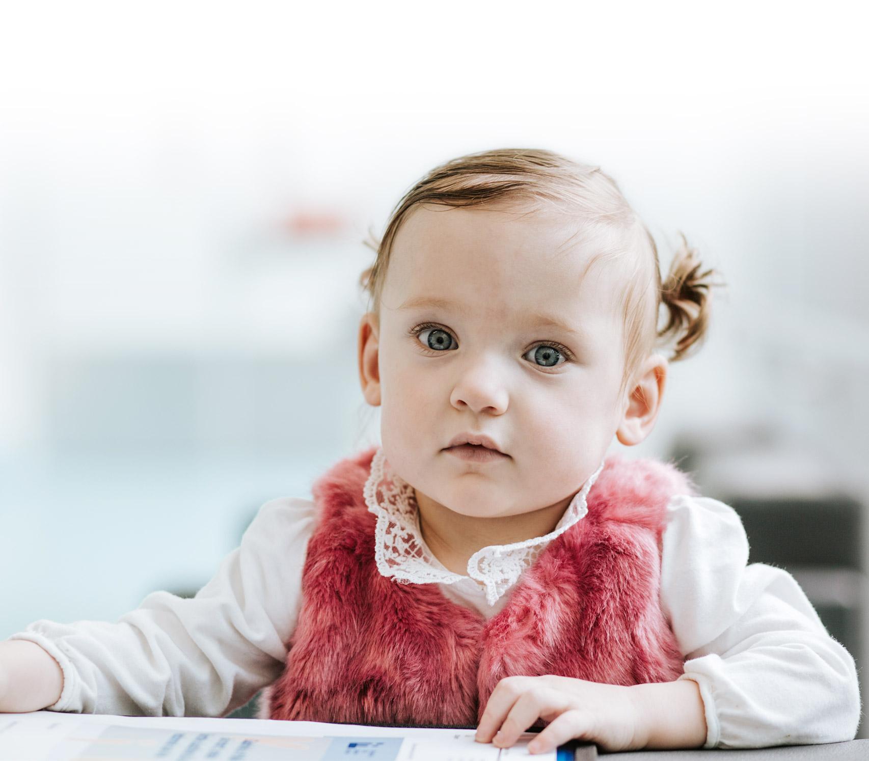 Olivia, une jeune patiente née prématurément à Sainte-Justine, pose fièrement, tout sourire.